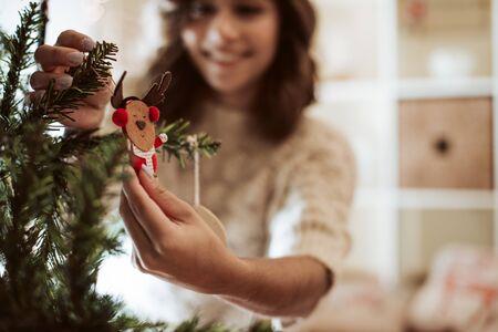 Vrouw versieren kerstboom thuis - Winterseizoen Stockfoto