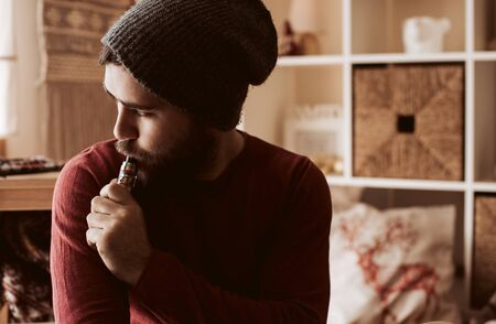 Trendy man using a vaper - Christmas and Winter Season
