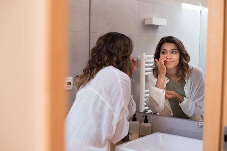 Beautiful woman in a modern , d,bathroom  moisturizing her skin  - Stock Photo