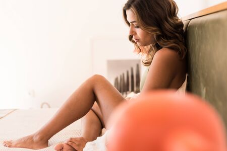 Modern and natural woman sitting on the bed with sexy clothes