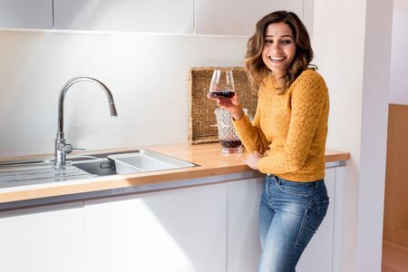 Woman drinking a glass of wine in a modern kitchen