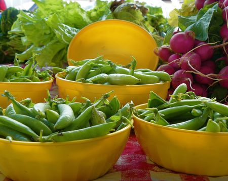 Snow peas displayed in yellow bowls on a red-and-white tablecloth at a farmers market