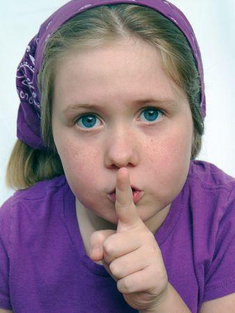 Una chica rubia con grandes ojos azules tiene un dedo a sus labios como si ella est� diciendo,  Foto de archivo - 3199071