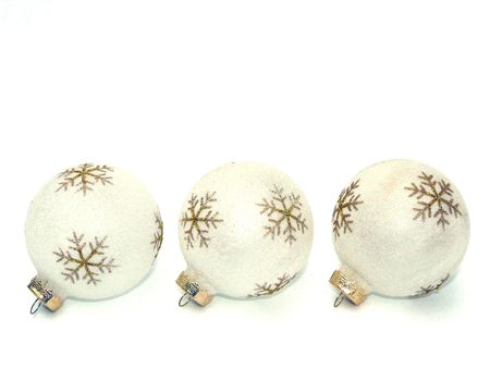 Three white ball-shaped Christmas or holiday ornaments decorated with gold snowflakes are lined up in a row on a white background photo