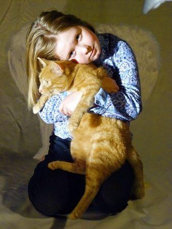 A cute little blond girl wearing angel wings hugs her big orange tabby cat Stock Photo