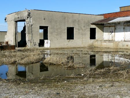 Abandoned Building Reflected in Standing Water