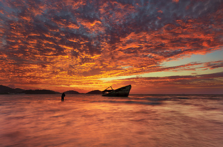 wrecked: fiery sky over a wrecked boat