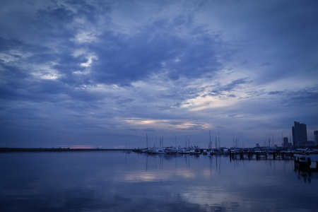 Yachts on peaceful water, breakwater on horizon and a bluish sky. photo