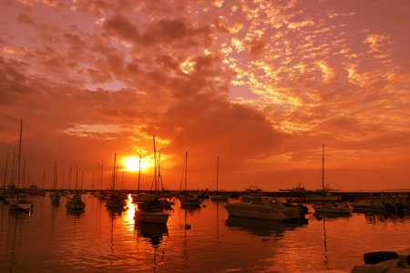Sun is like a rushing meteor towards the yachts on calm water. photo