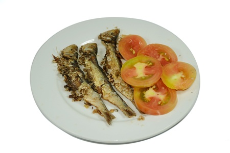 Exotic crunchy dried fish with sliced tomatoes (clipping path included).   photo