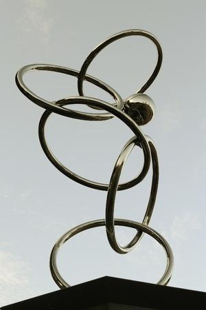 Artistic stainless metal rings, shot taken against gray sky. Stock Photo - 11958423