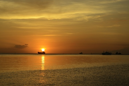 Beautiful sunset with boat and ships in silhouette at the horizon, located at Manila bay Philippines.   photo