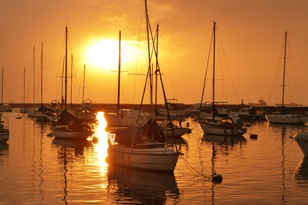dramatic sun and sailboat reflection over calm water during sunset.