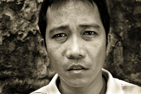 closeup artistic monochrome emotional portrait of good-looking gorgeous man standing against an old wall background  photo