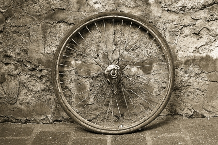 antique bicycle wheel isolated against old wall background  photo