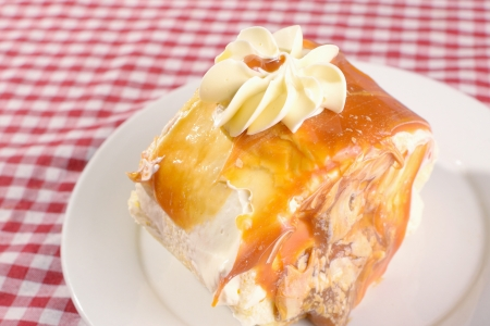 mouthwatering: top angle photo of mouth-watering slice of dulce de leche roll with vanilla buttercream icing on top and caramel filling  Stock Photo