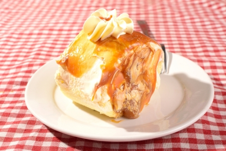 mouthwatering: mouth-watering slice of dulce de leche roll with vanilla buttercream icing on top and caramel filling  Stock Photo