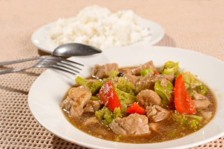 brocoli: plate of pork brocoli stewed in soy sauce, with plate of rice, fork, spoon in the background