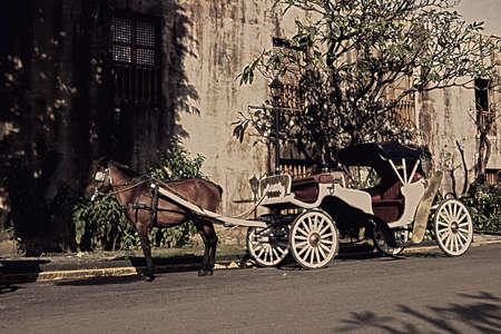 manila: pan shot of red horse-drawn carriage at fort Santiago Manila. Stock Photo