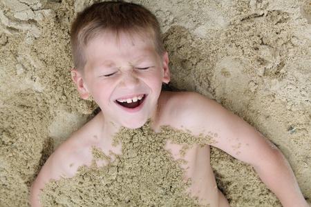 bury: Boy buried in sand Stock Photo