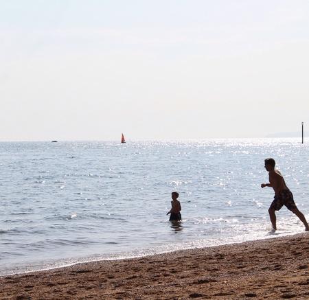 Man saving a boy at the Coast  Stock Photo