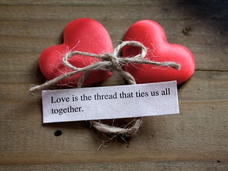 tender sentiment: Two silky love hearts next to a loving quote and a tied bow Stock Photo