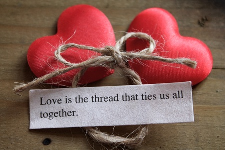 Two silky love hearts next to a loving quote and a tied bow Stock Photo