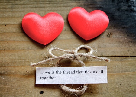 adoration: Two silky love hearts next to a loving quote and a tied bow Stock Photo