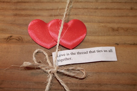 tender sentiment: Two silky love hearts next to a loving quote and thread Stock Photo