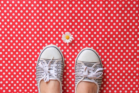 surface: A daisy and shoes on a polka dot surface Stock Photo