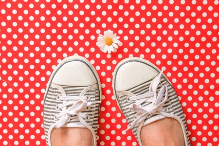 dot surface: A daisy and shoes on a polka dot surface Stock Photo