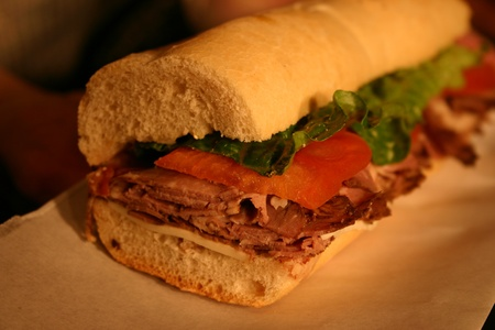 A roast beef hoagie loaded with lettuce and tomatoes photo