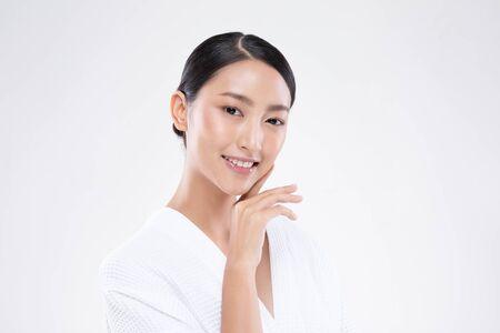 Hermosa mujer asiática tocando la suave sonrisa de la mejilla con la piel limpia y fresca Felicidad y alegre con emocional positivo, aislado sobre fondo blanco, concepto de belleza y cosméticos