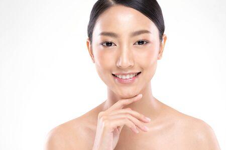 Schöne junge asiatische Frau, die beim Berühren des Kinns so glücklich und fröhlich mit gesunder, sauberer und frischer Haut aussieht, isoliert auf weißem Hintergrund, Schönheitskosmetik-Konzept