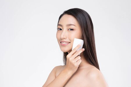 Attractive Charming Asian young woman smile and using tissue with toner for cleaning make up feeling so fresh and clean with healthy skin,isolated on white background,Beauty Cosmetics Concept Stock Photo