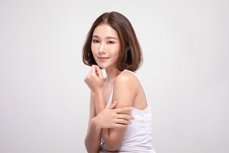 Beautiful Young Asian Woman with short hair Looking While Touching Chin feeling so happy and cheerful with healthy Clean and Fresh skin,isolated on white background,Beauty Cosmetics Concept 스톡 콘텐츠