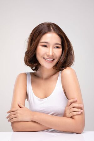 Beautiful Asian woman with short hairs looking While smile with clean and fresh skin Happiness and cheerful with positive emotional,isolated on gray background,Beauty and Cosmetics Concept 스톡 콘텐츠