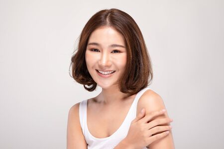 Beautiful Young Asian Woman with short hairs Touching Shoulder feeling so happy and cheerful with healthy Clean and Fresh skin,isolated on gray background,Beauty Cosmetology Concept