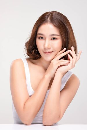 Beautiful Young Asian Woman with short hair Holding Hands smile feeling so happy and cheerful with healthy Clean and Fresh skin,isolated on gray background,Beauty Cosmetics Concept