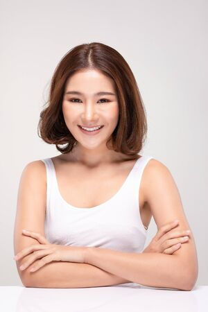 Beautiful Asian woman with short hair looking at camera smile with clean and fresh skin Happiness and cheerful with positive emotional,isolated on gray background,Beauty and Cosmetics Concept