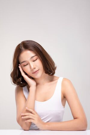 Beautiful Asian young woman close her eyes touching soft cheek smile with clean and fresh skin Happiness and cheerful with positive emotional,isolated on white background,Beauty and Cosmetics Concept Фото со стока