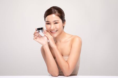 Beautiful Young Asian Woman with short hair Holding luxury cream jar smile feeling so happy and cheerful with healthy Clean and Fresh skin,isolated on gray background,Beauty Cosmetics Concept
