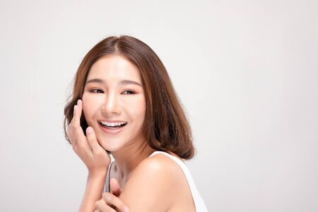 Beautiful Asian young woman touching soft cheek smile with clean and fresh skin Happiness and cheerful with positive emotional,isolated on gray background,Beauty and Cosmetics Concept