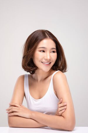 Beautiful Asian woman with short hairs looking While smile with clean and fresh skin Happiness and cheerful with positive emotional,isolated on gray background,Beauty and Cosmetics Concept Фото со стока