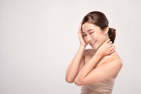Beautiful Asian young woman close her eyes touching soft cheek smile with clean and fresh skin Happiness and cheerful with positive emotional,isolated on gray background,Beauty and Cosmetics Concept Фото со стока