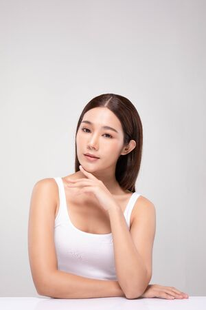 Beautiful Young Asian Woman Looking While Touching Chin feeling so happy and cheerful with healthy Clean and Fresh skin,isolated on gray background,Beauty Cosmetics Concept Фото со стока