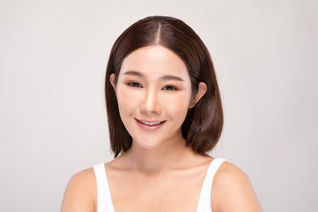 Beautiful Asian woman looking at camera smile with clean and fresh skin Happiness and cheerful with positive emotional,isolated on gray background,Beauty and Cosmetics Concept Фото со стока