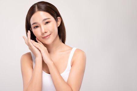 Beautiful Asian young woman holding hands smile with clean and fresh skin Happiness and cheerful with positive emotional,isolated on gray background,Beauty and Cosmetics Concept