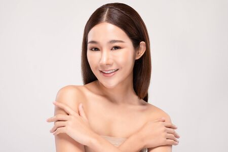 Beautiful Young Asian Woman Looking While Touching Shoulder feeling so happy and cheerful with healthy Clean and Fresh skin,isolated on gray background,Beauty Cosmetology Concept Фото со стока