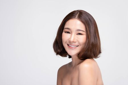 Beautiful Asian woman with short hairs looking at camera smile with clean and fresh skin Happiness and cheerful with positive emotional,isolated on gray background,Beauty and Cosmetics Concept